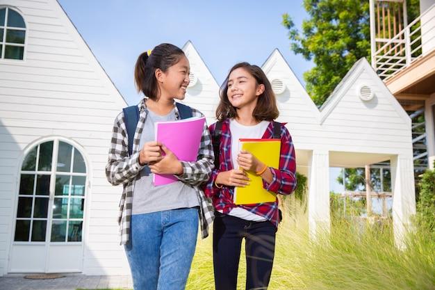 Twee tiener azië en europese meisjes van studentenvrienden het gelukkige naar universiteit gaan of school, diverse behoren tot een bepaald ras