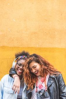 Twee tiener latijnse meisjes die zich over een gele muur verenigen