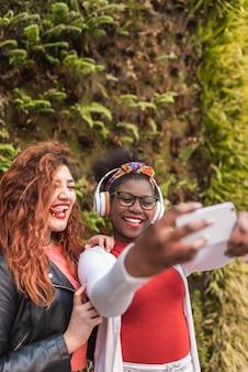 Twee tiener vrouwelijke vrienden nemen een selfie buitenshuis.