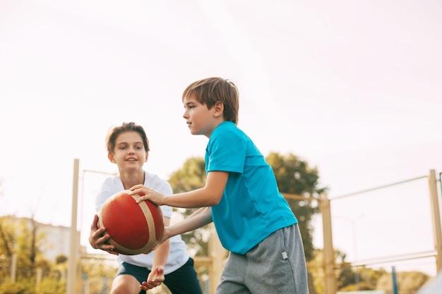 Twee tienerjongens spelen basketbal op de speelplaats. atleten vechten om de bal in het spel