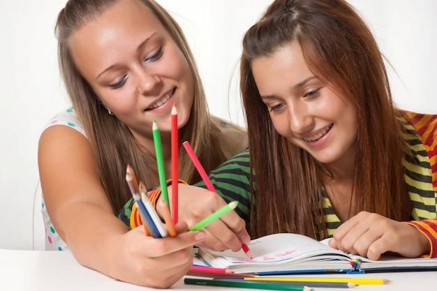 Twee tienermeisjes glimlachen en geschilderd in het boek