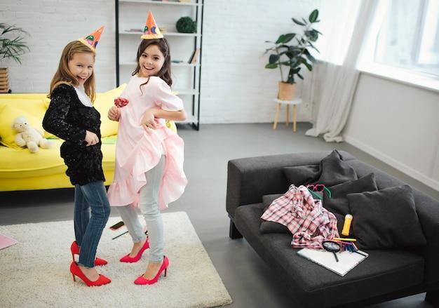 Twee tienermeisjes hebben plezier samen in de kamer. ze dansen en poseren. brunette houdt lolly in de hand.