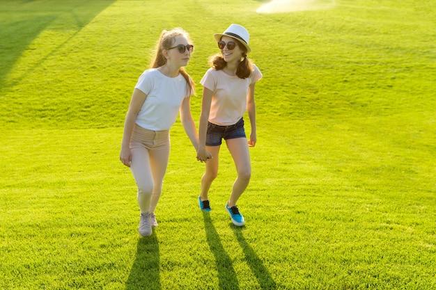 Twee tienermeisjes houden handen op het groene gras in het park op een hete de zomerdag