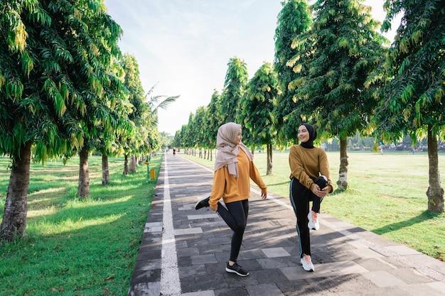Twee tienermeisjes in hoofddoeken die hun beenspieren strekken door het gebogen been met hun armen op te tillen en vast te houden voordat ze in het park gaan joggen