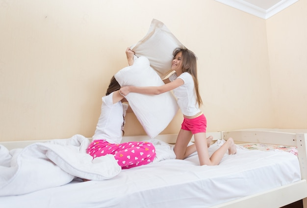 Twee tienermeisjes in pyjama die vechten met kussens