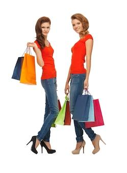 Twee tienermeisjes in rode t-shirts met boodschappentassen