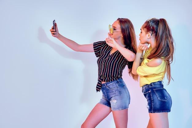 Twee tienermeisjes in zomerkleren permanent in studio en selfie maken op witte achtergrond