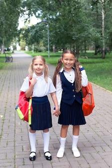 Twee tienermeisjes lopen in de zomer in het park, praten, lopen na school en universiteit, houden elkaars hand vast, beste vrienden keren na de training terug naar huis. vrije ruimte voor tekst kopiëren.