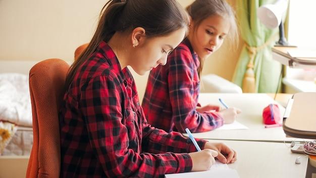 Twee tienermeisjes op zelfisolatie die thuis studeren en schoolhuiswerk doen.