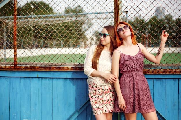 Twee tienermeisjes poseren in de buurt van de schoolbaan, het concept van de adolescentie-mode