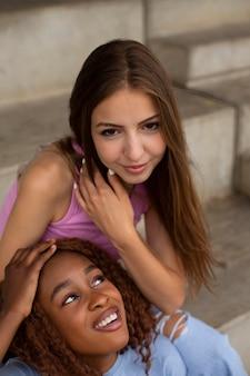 Twee tienermeisjes poseren samen voor een selfie buitenshuis