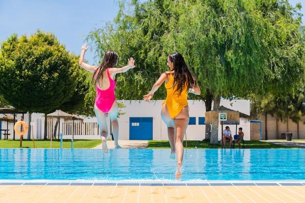 Twee tienermeisjes springen in een zwembad. twee meisjes springen in een zwembad
