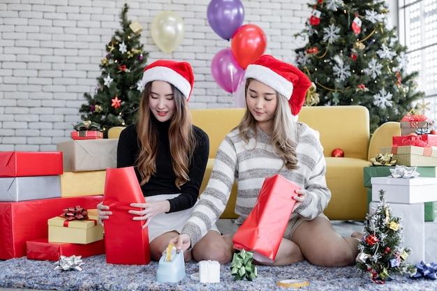 Twee tienermeisjes verpakken de geschenkdoos op het kerstfestival thuis met een glimlach en gelukkig.