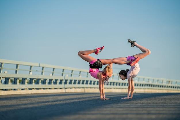 Twee tienermeisjes voeren buiten tegen een blauwe hemel een acrobatisch element uit
