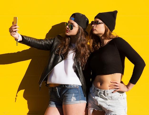 Twee tienermeisjes vrienden in hipster outfit buiten maken selfie op een telefoon.