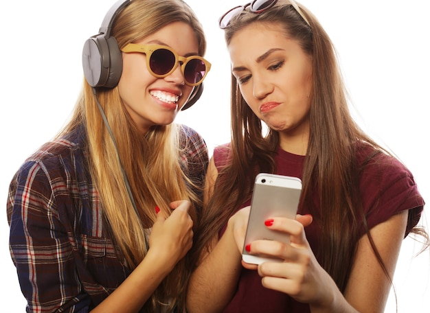 Twee tienermeisjes vrienden in hipster outfit maken selfie op een telefoon.
