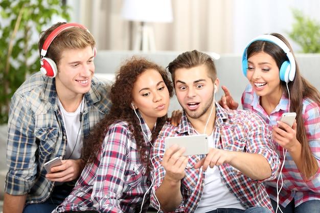 Twee tienerparen luisteren naar muziek en nemen foto met mobiele telefoon in de woonkamer