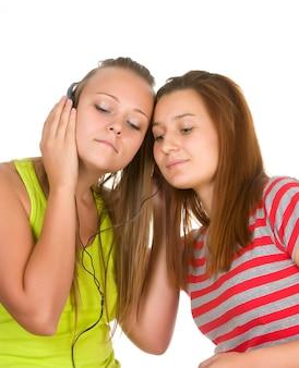 Twee tieners die aan muziek op uw mobiele telefoon luisteren die op wit wordt geïsoleerd