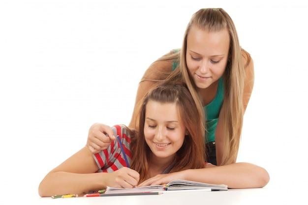 Twee tieners die en boek glimlachen lezen dat op wit wordt geïsoleerd