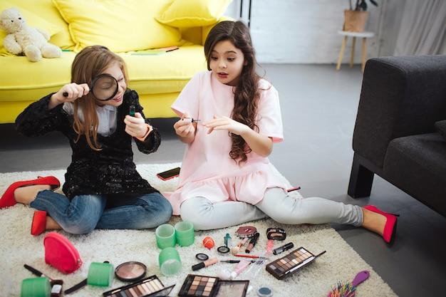 Twee tieners die op vloer in ruimte zitten. het meisje op linkerzijde bekijkt fles door lenz. tiener rechts zet wat nagellak. ze kijkt verbaasd.