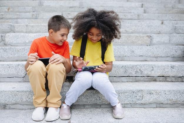 Twee tieners, een jongen en een afrikaans meisje, zitten op de trap met een smartphone in hun handen.