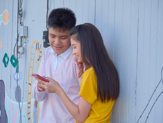 Twee tieners gebruiken hun smartphones buitenshuis