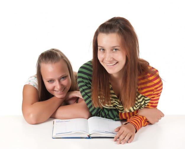 Twee tieners lezen geïsoleerd op wit