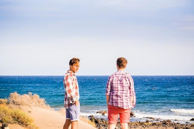 Twee tieners op het strand alleen en geïsoleerd kijken naar de zee en praten samen - volwassenen aan zee die plezier hebben en zich voorbereiden om te gaan surfen