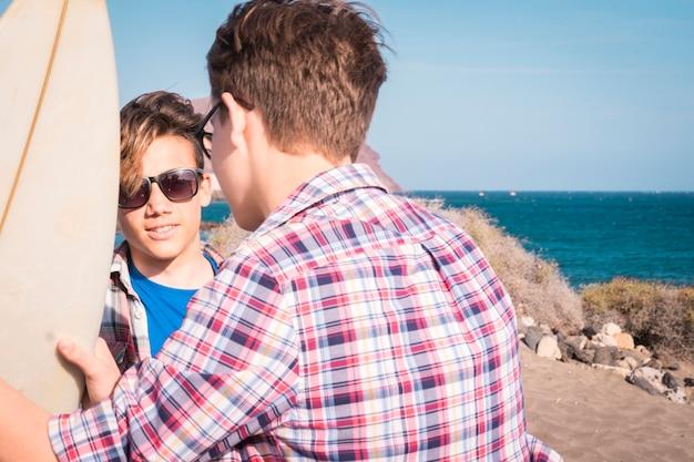 Twee tieners op het strand met één surftafel praten en samen plezier hebben - vakanties aan het zee-levensstijlconcept