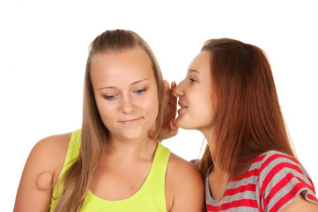 Twee tieners roddelen geïsoleerd op wit