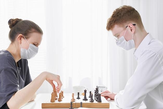 Twee tieners schaken tijdens quarantaine vanwege coronavirus pandemie. jongen en meisje spelen bordspellen