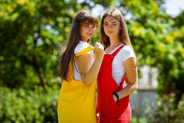 Twee tieners tweeling in een gele en rode schooljurk in de middag