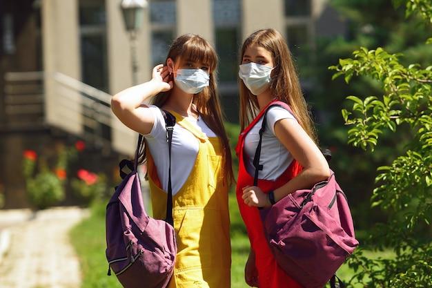 Twee tieners tweelingen in een gele en rode schooljurk met paarse rugzakken lopen naar school