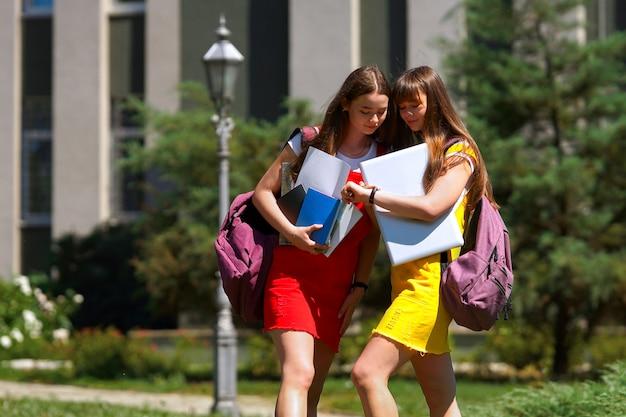 Twee tieners-tweelingen in een gele en rode schooljurk met paarse rugzakken staan 's middags buiten de school