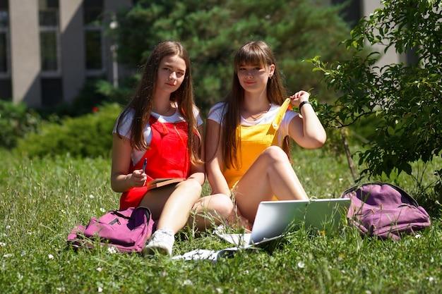 Twee tieners-tweelingen in een gele en rode schooljurk met paarse rugzakken zitten 's middags buiten de school