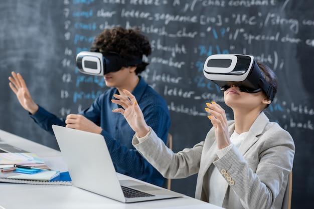 Twee tienerstudenten in vr-hoofdtelefoons die door bureau tegen bord zitten en aan presentatie of seminar in klaslokaal deelnemen tijdens les