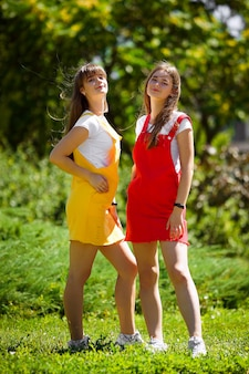 Twee tienertweelingen in een gele en rode schooljurk in de middag