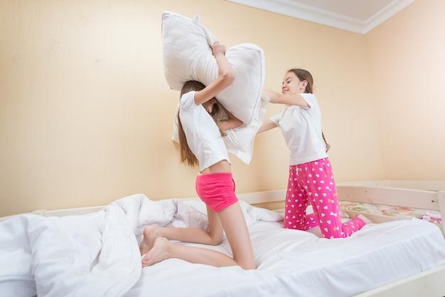 Twee tienerzussen hebben kussengevecht op bed