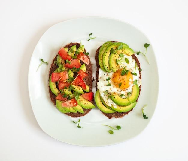 Twee toasts van donker brood met plakjes avocado, gehakte tomaten, gebakken ei en microgroen. ontbijt concept.