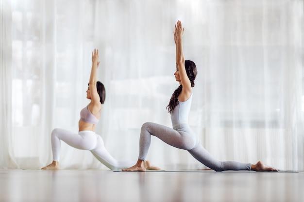 Twee toegewijde flexibele blanke meisjes in crescent lunge on the knee yogapositie. yoga studio interieur.