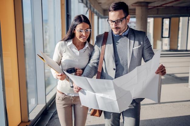 Twee toegewijde hardwerkende positieve architecten lopen in het bouwproces en kijken naar blauwdrukken. nieuwe bouw van een zakencentrum.