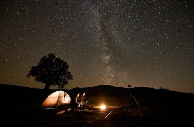 Twee toeristen bij brandend kampvuur voor tent, fotocamera op statief onder donkere sterrenhemel.