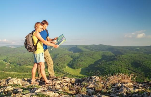 Twee toeristen op de berg lezen de kaart. mens bovenop klip.