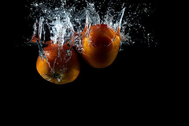 Twee tomaten spatten op water