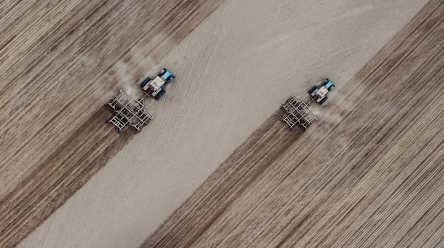 Twee tractoren ploegen het bovenaanzichtveld
