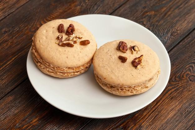 Twee traditionele franse beige macarons op plaat