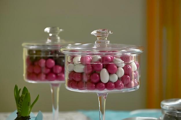 Twee transparante glazen containers gevuld met gekleurde snoepjes als decoratief element.