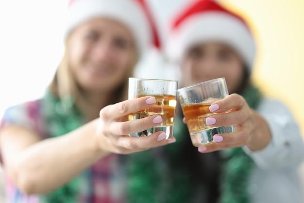 Twee transparante glazen met alcoholische drank sluiten omhoog samen.
