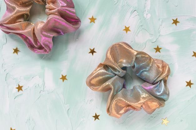 Twee trendy holografische scrunchies en gouden sterren confetti op groene tafel