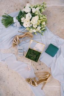 Twee trouwringen en bruidsaccessoires op een witte stof met een boeket bloemen en sandalen